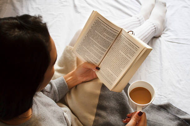 girl reading book and drinking coffee in bed in the morning - foto de stock