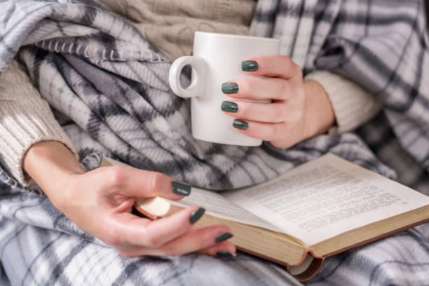 mädchen lesen buch und halten tasse kaffee und bedeckt mit retro-decke - herbst nagellack stock-fotos und bilder