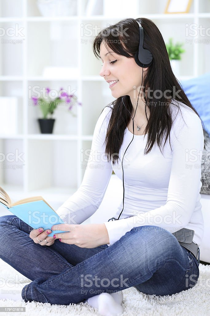 girl reading book and listening music royalty-free stock photo