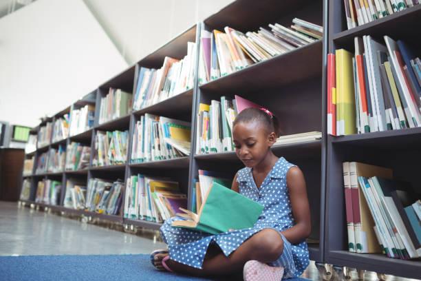 mädchen lesen buch vom regal in der bibliothek - leseunterricht stock-fotos und bilder