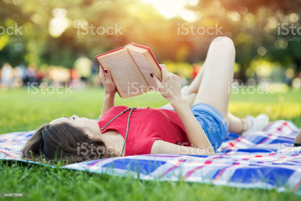 Girl reading book in the park stock photo
