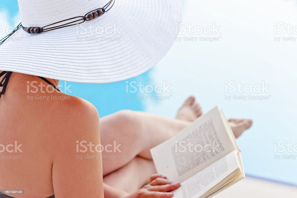 Girl  reading  book near the pool, sitting in  lounge chair royalty-free stock photo