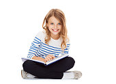 education and school concept - little student girl sitting on floor and reading book