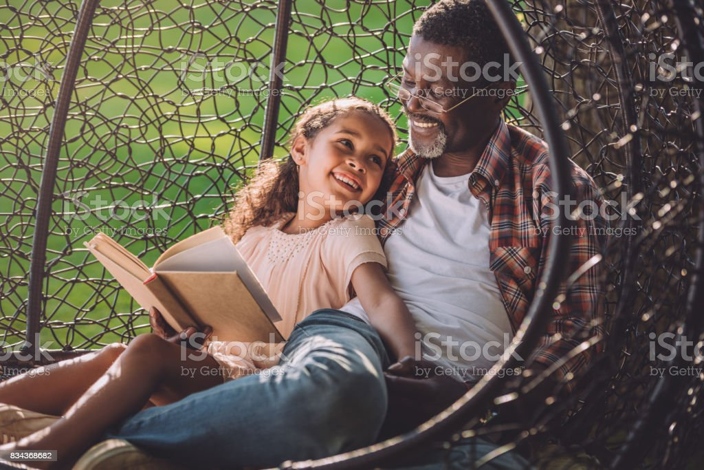 girl reading book while sitting in swinging hanging chair with granddad stock photo