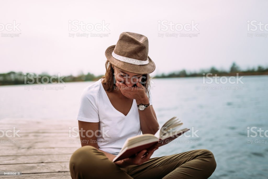 Girl reading funny book and laughing.