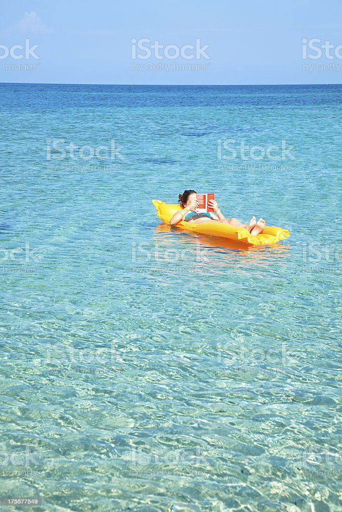 Girl reading in a beach royalty-free stock photo