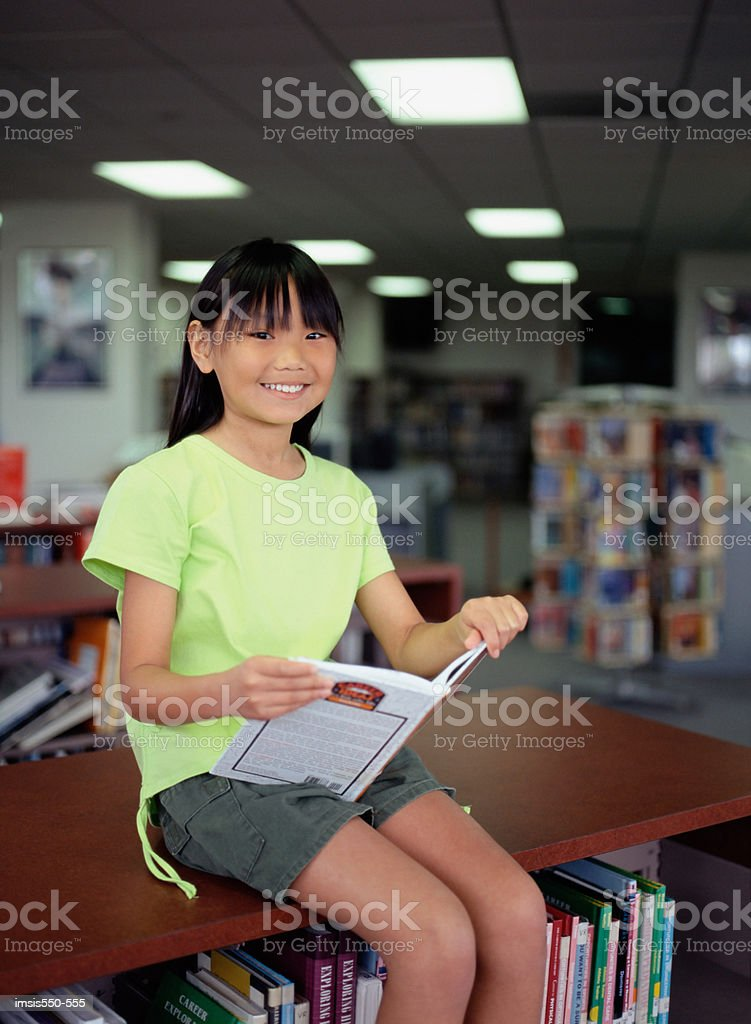 Girl reading in library royalty-free stock photo