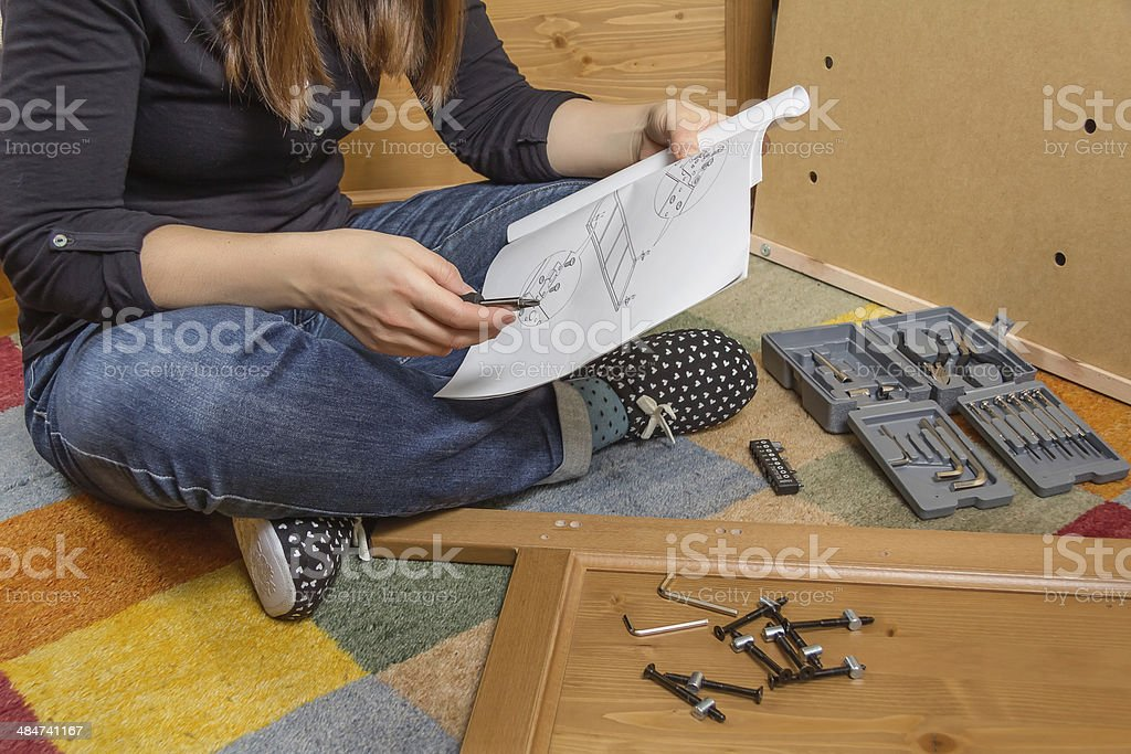Girl reading instructions to assemble furniture stock photo