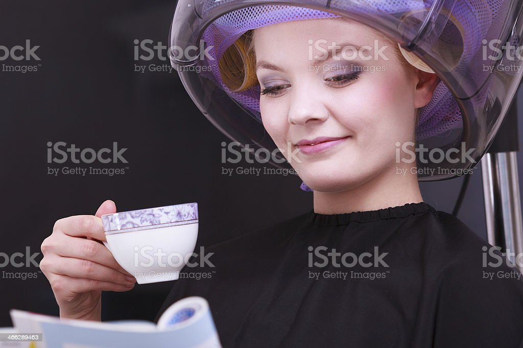 Girl reading magazine drinking coffee. Hairdryer in hair beauty salon stock photo