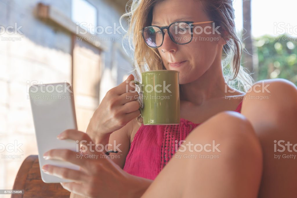 Girl reading news on a smart phone and drinking morning coffee. stock photo