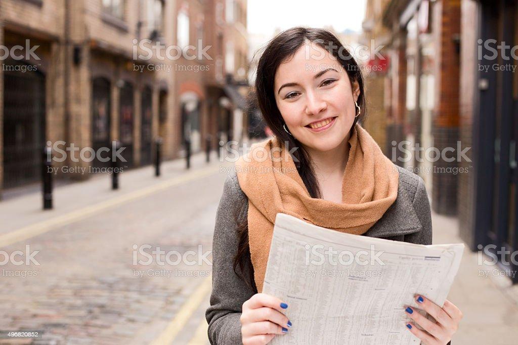 girl reading newspaper stock photo