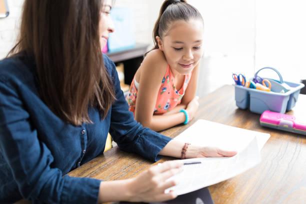 Mädchen lesen Noten durch Lehrer am Tisch im Haus gehalten – Foto