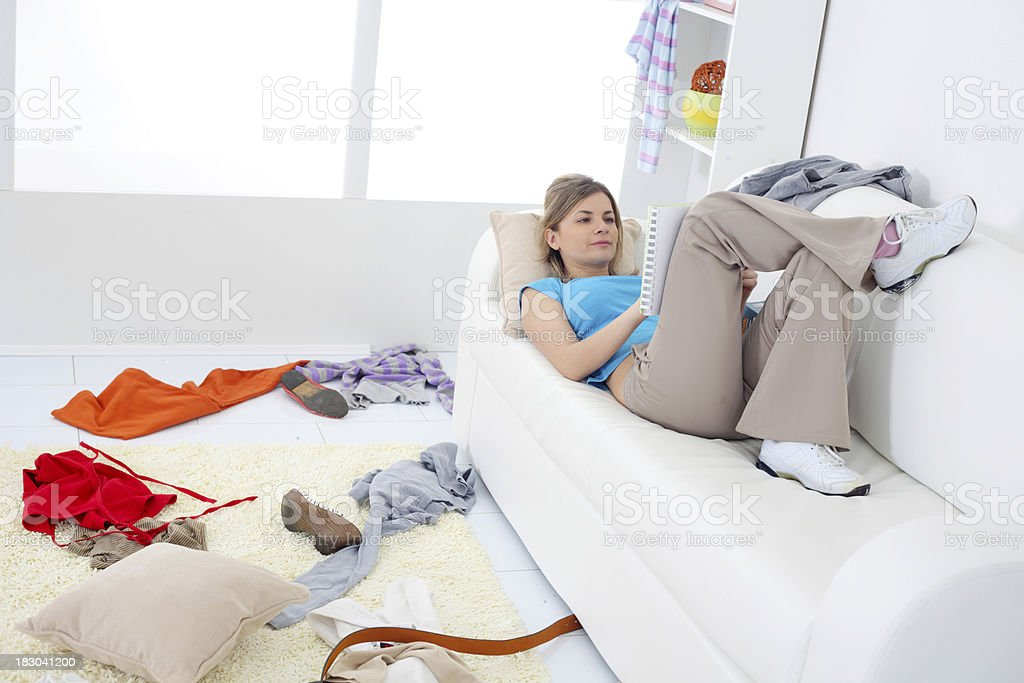 Girl reading on a sofa. Mess in the room. stock photo
