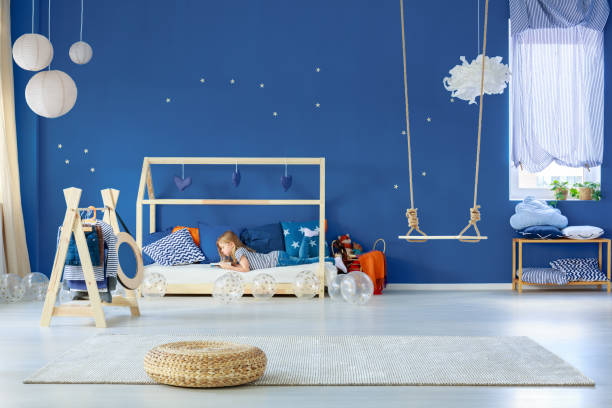 mädchen lesen auf bett - marineblau schlafzimmer stock-fotos und bilder