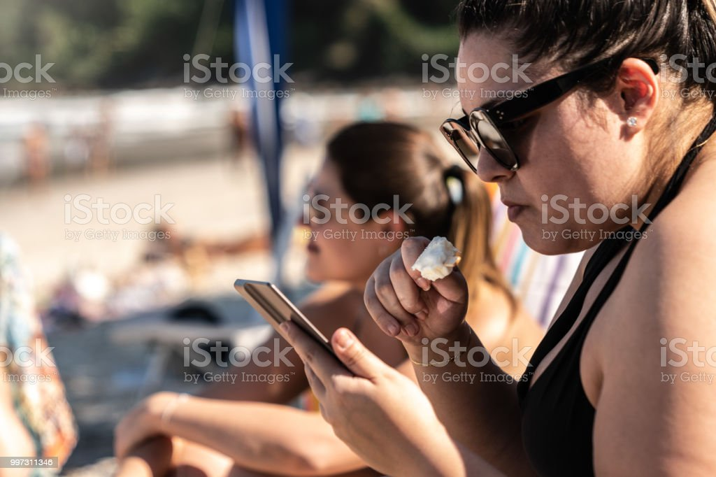 Girl Reading On Ebook At Beach Summer Day In Brazil Stock