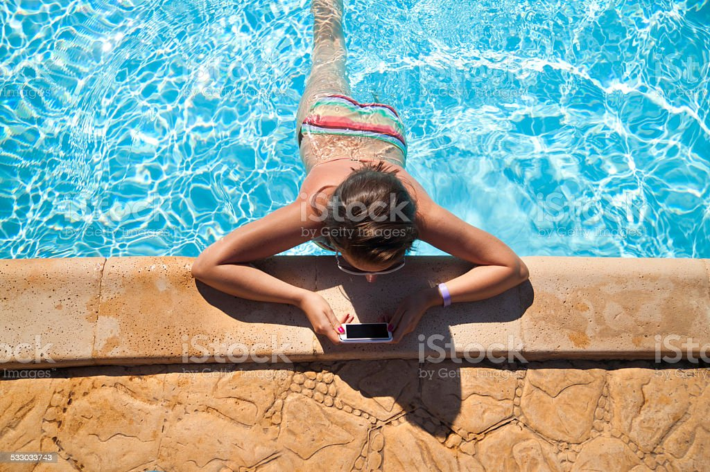 Girl reading on smartphone in the swimming pool stock photo