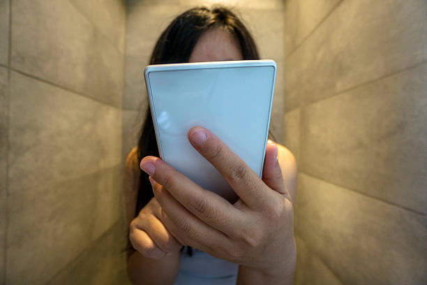 girl reading smart phone in toilet - foto de acervo