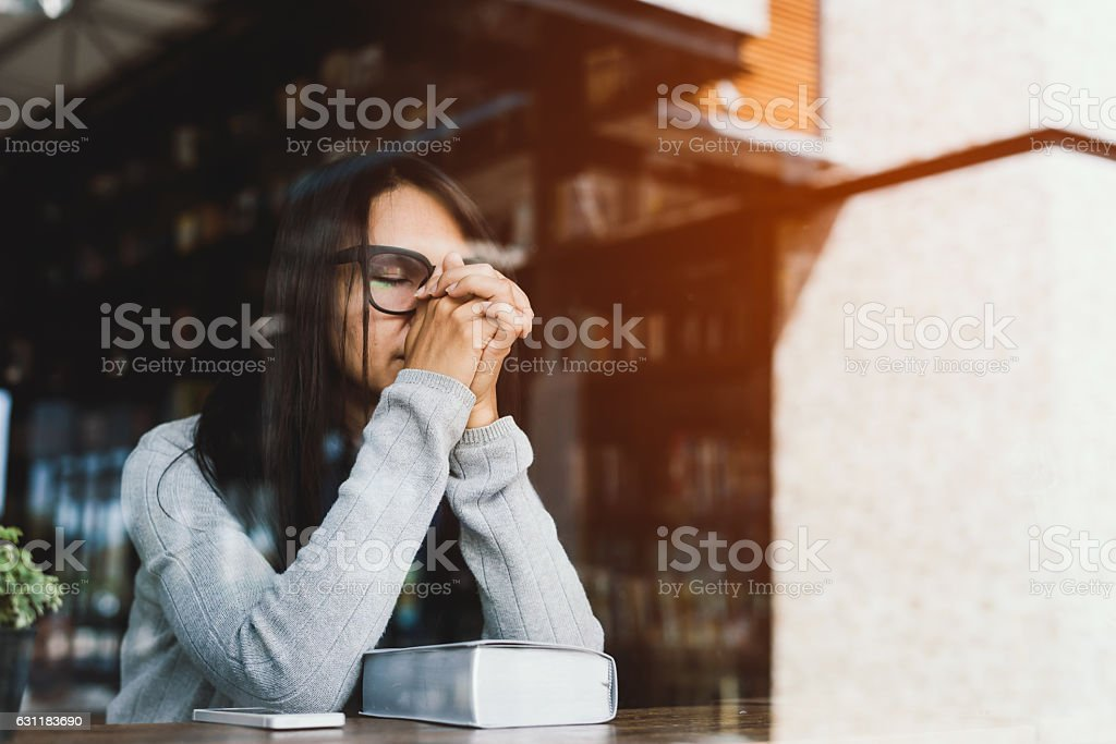 Girl reading the Bible in the library cafe. stock photo