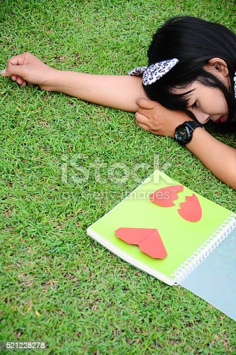 815359666 istock photo Girl Reading the Book of Heart on Grass 521228278