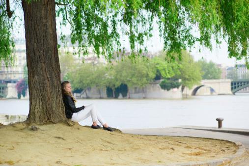 Girl reading under a tree near Seine