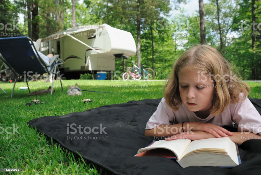 Girl reading while camping royalty-free stock photo