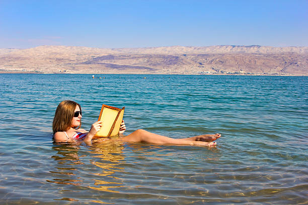 girl reads a book floating in Dead Sea in Israel beautiful young woman reads a book floating in the waters of the Dead Sea in Israel historical palestine stock pictures, royalty-free photos & images