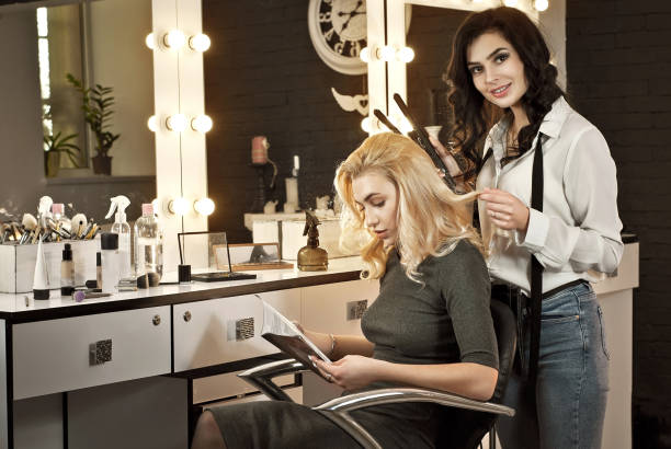 A girl reads a magazine in a beauty salon. The wizard makes a hairstyle to the client. Blonde and brunette with backlit mirror background. Delicate and fun customer service. A girl reads a magazine in a beauty salon. The wizard makes a hairstyle to the client. Blonde and brunette with backlit mirror background. Delicate and fun customer service. saloon stock pictures, royalty-free photos & images