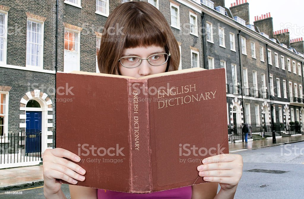 girl reads over English Dictionary and house foto