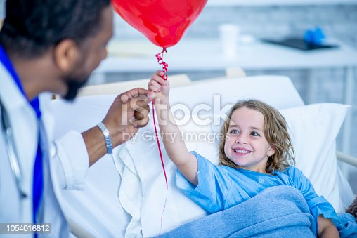 istock Girl receives a red balloon while lying in a hospital bed 1054016612