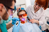 Girl receiving dental filling drying procedure.