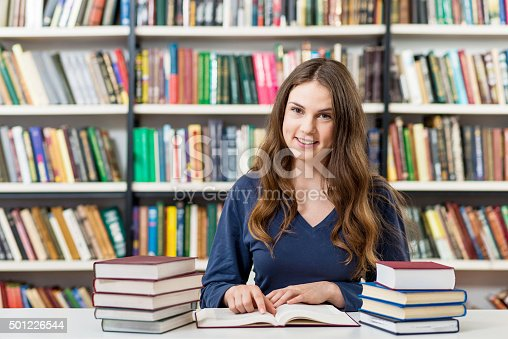 istock girl reding books in the library, studying 501226544