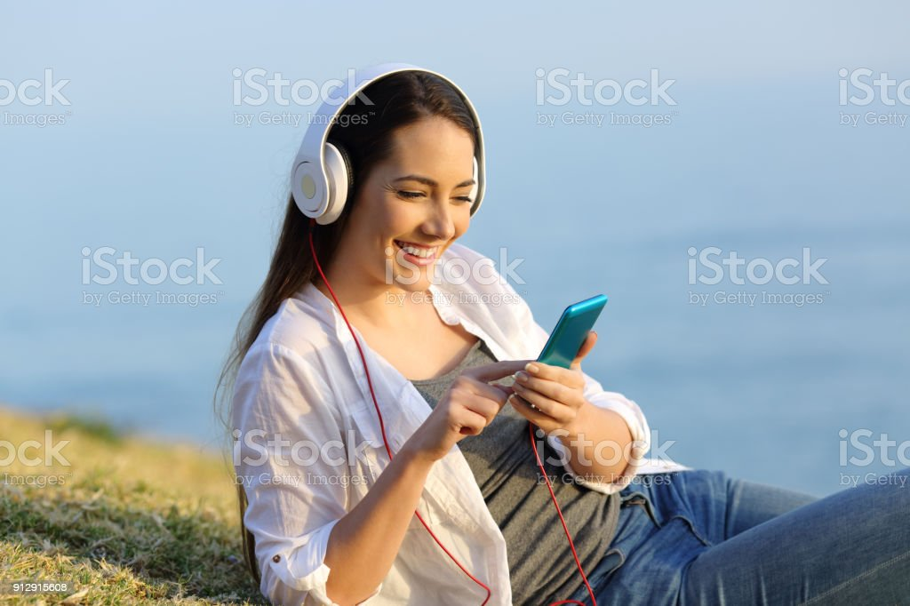 Girl relaxed listening to music online outdoors stock photo