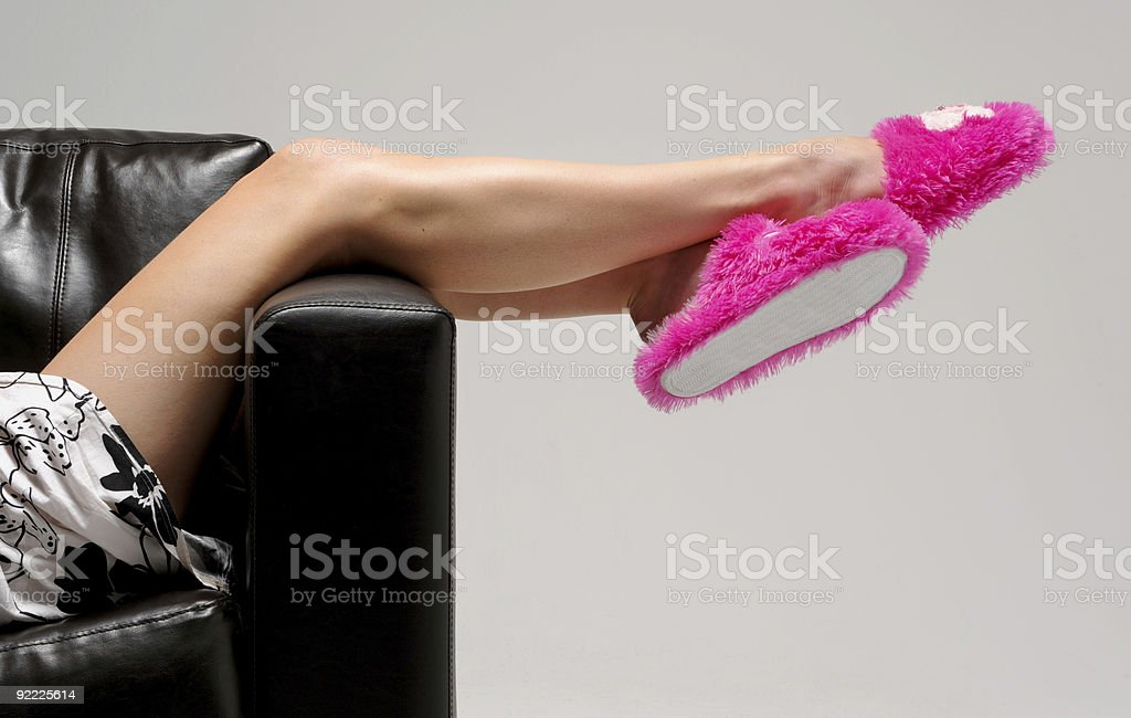 Girl relaxes with pink slippers stock photo