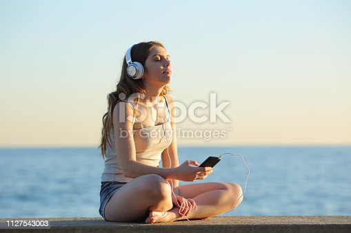 Girl relaxing listening to music from smart phone