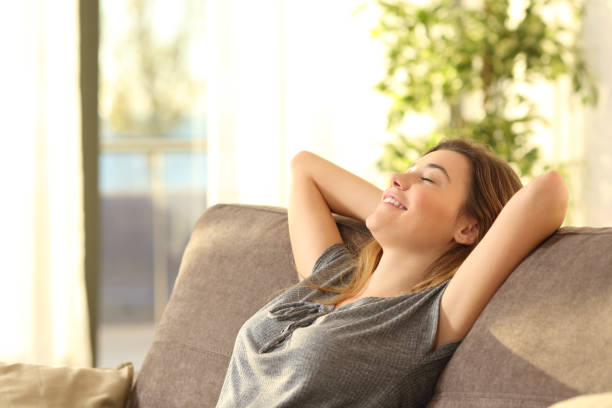 girl relaxing on a sofa at home - comfort stock photos and pictures