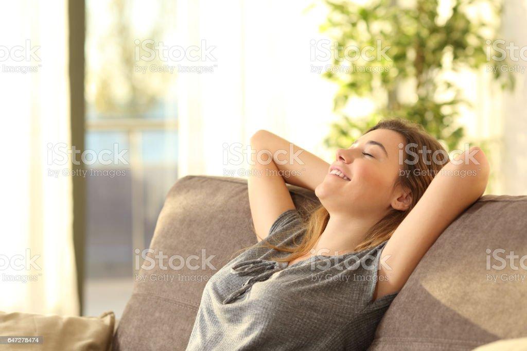 Relaxando em um sofá em casa de menina - foto de acervo