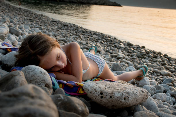 girl relaxing on  beach of pebbles at the sunset - girl alone in swimsuit stock photos and pictures