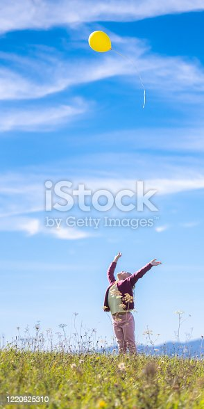 Little girl releasing yellow balloon against blue sky while standing in field.