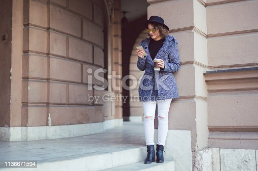 Girl relies on a pillar with a cup of coffee in one and a phone in her other hand, wearing gray coat and black hat