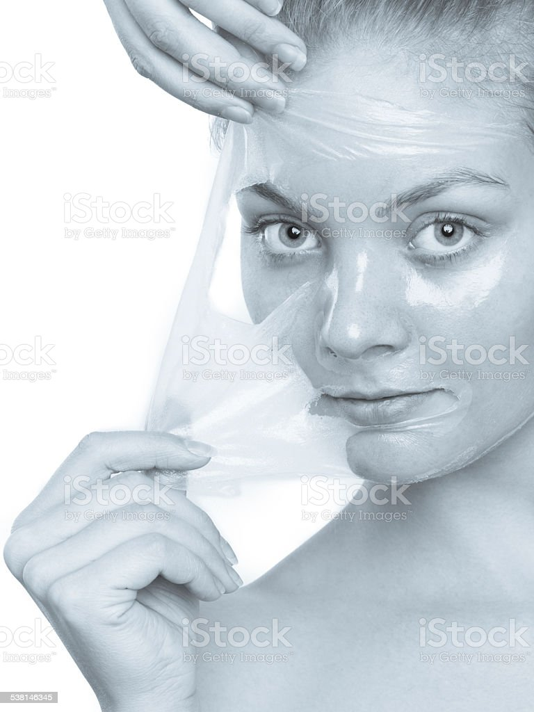 girl removing facial peel off mask stock photo
