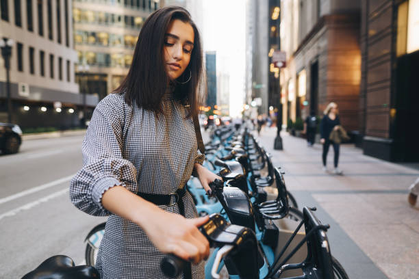 girl renting a city bike from a bike stand stock photo