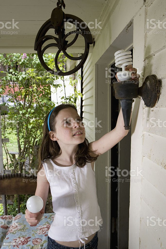 Girl replacing energy efficient bulb on porch royalty-free stock photo
