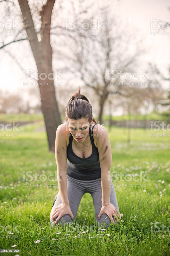 girl resting girl crouching down after running stock photo