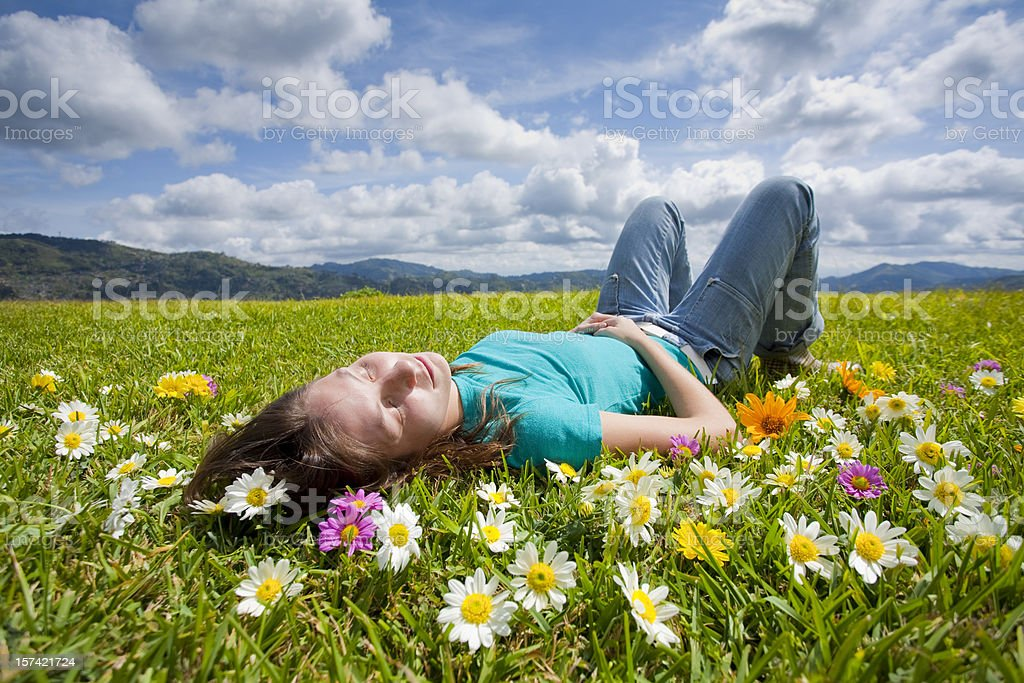 A girl resting in a field of flowers in a meadow royalty-free stock photo