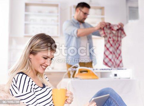 802472024 istock photo Girl resting on sofa while man ironing 907686738