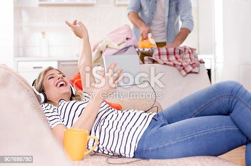 802472024 istock photo Girl resting on sofa while man ironing 907686780
