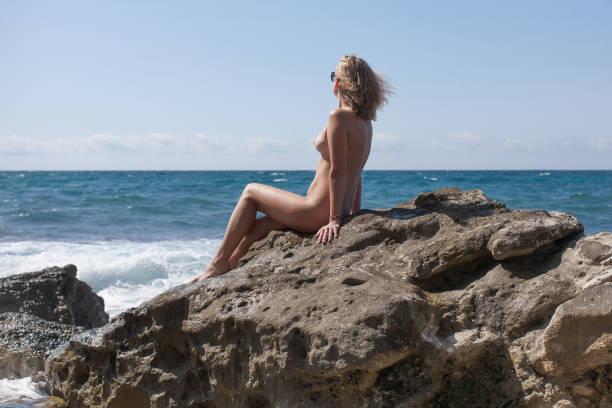 ruht auf wilden felsigen strand mädchen - fkk strand stock-fotos und bilder