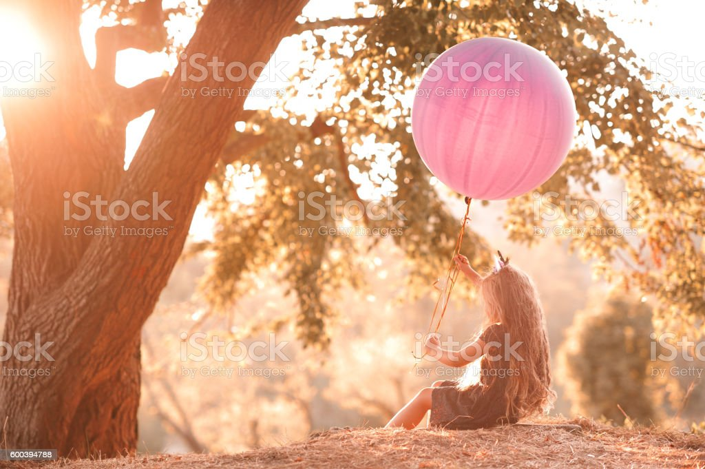 Girl resting outdoors at sunset stock photo