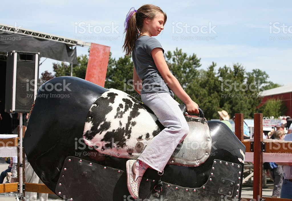 Girl Rides Mechanical Bull at Rodeo stock photo