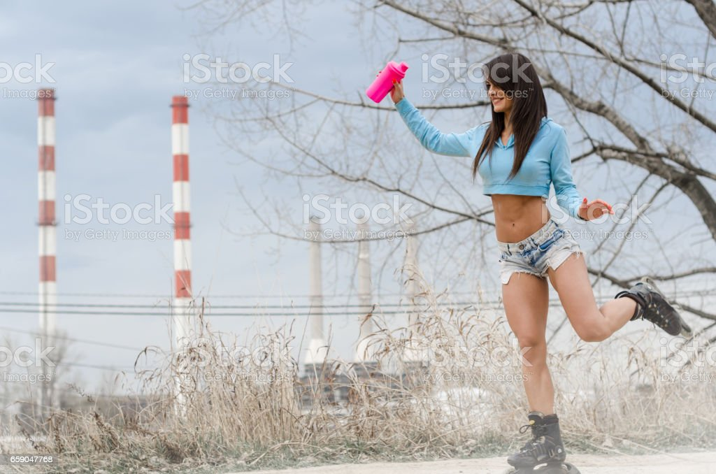 Girl rides roller skates in front of factories and polluted chimneys, sport against pollution foto